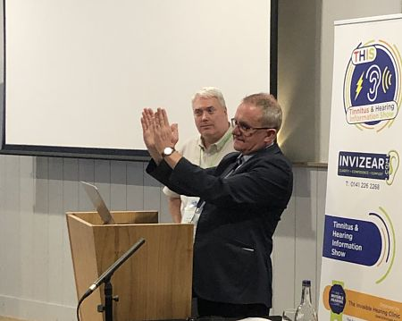 Professor David Baguley stands at a lecturn and explains one of his concepts during the Tinnitus and Hearing Information Show (THIS 2019) with hand gestures as show organiser Alan Hopkirk looks on.